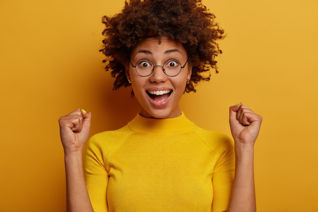 네, 해냈습니다! 기분 좋은 어두운 피부를 가진 여자는 주먹을 움켜 쥐고 행복하게 보이며 캐주얼 한 옷을 입고 노란색 벽에 서서 승자처럼 느껴집니다. 사람, 감정, 라이프 스타일