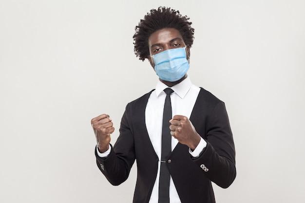 はい、勝ちます!拳で立って彼の勝利を祝うサージカルマスクと黒いスーツを着ている誇り高き若いハンサムな労働者の男の肖像画。灰色の背景に分離された屋内スタジオショット。