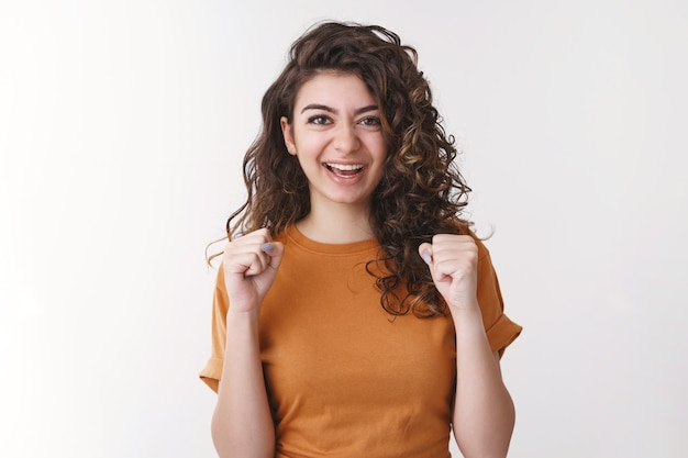 Yes lucky me. happy triumphing young joyful armenian woman curly-haired clench fists celebrating successful win lottery smiling say yeah, excited good positive result, standing white background