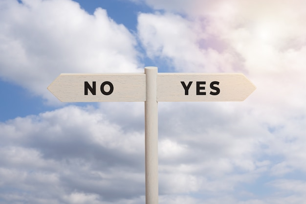 Yes or no concept. wooden sign post with text isolated on sky