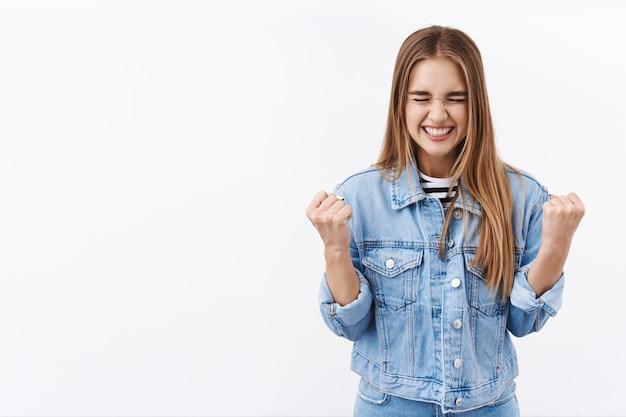 はい、彼女はそれをしました。勝利を喜んで、賞を獲得し、目標を達成し、目を閉じて明るい笑顔で拳ポンプ、目標を達成し、成功を祝い、白い壁に勝利する幸せで陽気なブロンドの女の子