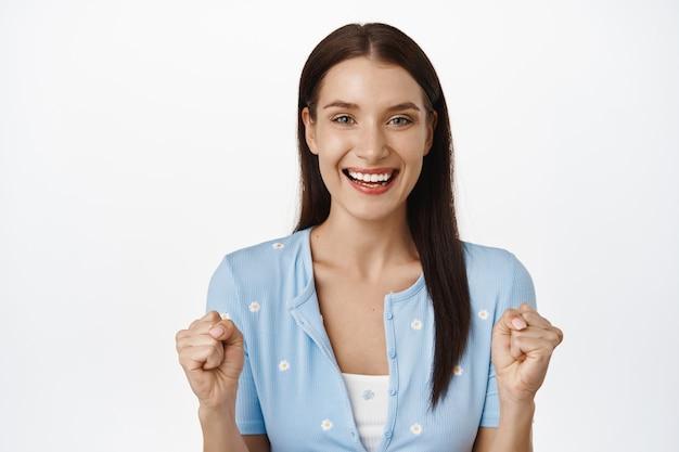 はい成功。幸せな満足の女性の拳ポンプ、握りこぶし、希望と自信を持って見て、肯定的な結果を待って、白で自分自身を励まします。