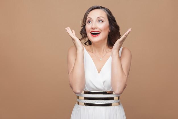 예! 성공 여자 이빨 미소와 기쁨 승리입니다. 흰 드레스, 붉은 입술, 짙은 곱슬머리를 한 감정적인 여성. 스튜디오 촬영, 실내, 베이지색 또는 밝은 갈색 배경에 격리