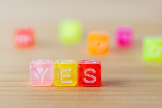 Yes text with color letters cubes on wooden background.