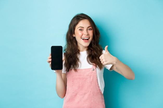 Sì, questo è buono. sorridente ragazza carina che mostra pollice in su e schermo dello smartphone vuoto, consigliando l'applicazione o il negozio online, in piedi su sfondo blu.