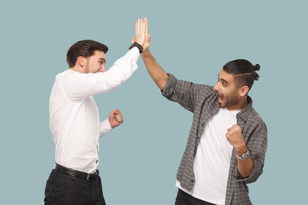 はい、やりました。一緒に勝利を祝って、こんにちは5つの手を与える2人の若いハンサムな幸せな満足しているひげを生やしたパートナーの表情プロフィール側面図。屋内スタジオショット、水色の背景で分離
