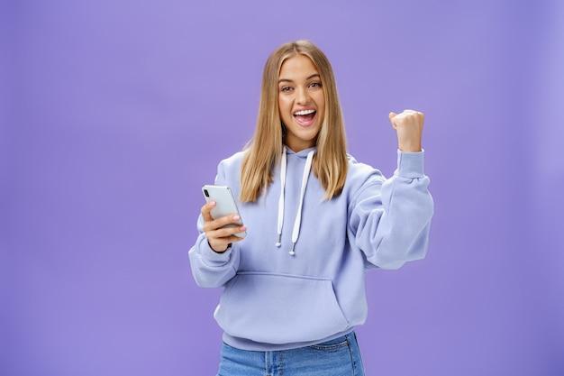 Да, мы сделали это. довольная взволнованная женщина в толстовке с капюшоном поднимает кулак на праздновании и жесте успеха, широко улыбаясь, торжествуя, держа смартфон, реагирующий на позитивные новости в мобильном телефоне над фиолетовой стеной