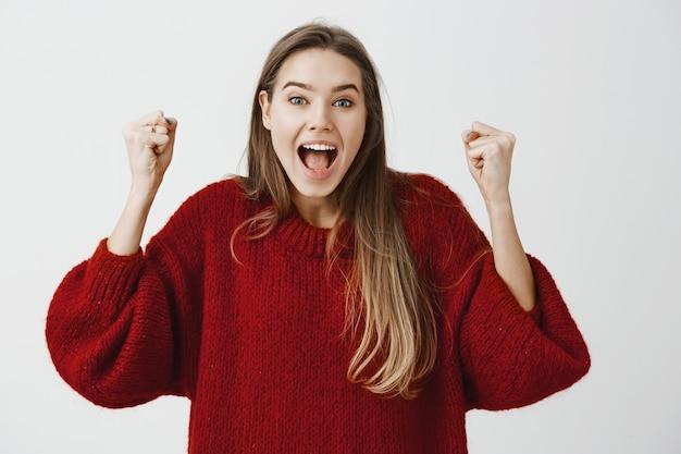 Sì, l'abbiamo fatto. ritratto di felice attraente donna caucasica che celebra la vittoria, saltando e sollevando i pugni chiusi da emozioni positive e felicità, urlando dal successo sul muro grigio