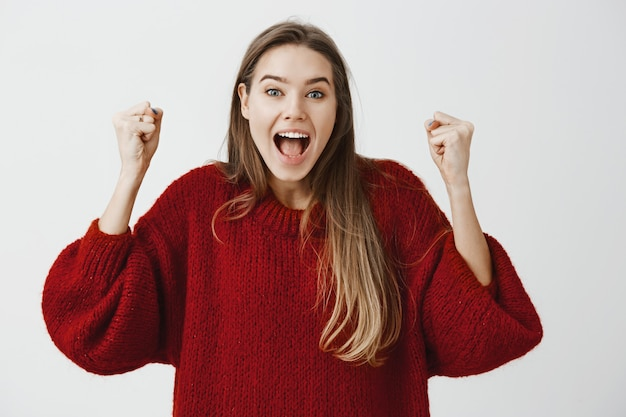 Да, мы сделали это. портрет счастливой привлекательной кавказской женщины празднуют победу, прыгают и поднимают сжатые кулаки от положительных эмоций и счастья, кричат от успеха над серой стеной