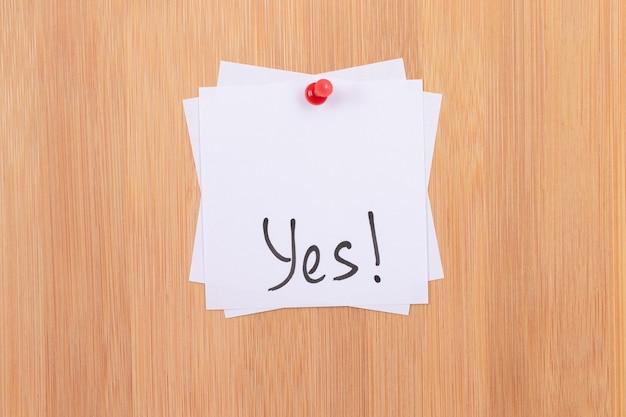 はい木製の掲示板に固定された「はい」と書かれた白い付箋