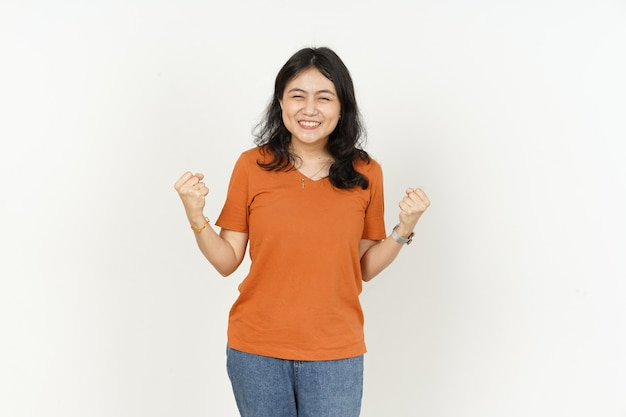 예, 흰색 배경에 격리된 주황색 티셔츠를 입은 아름다운 아시아 여성의 제스처를 이깁니다.