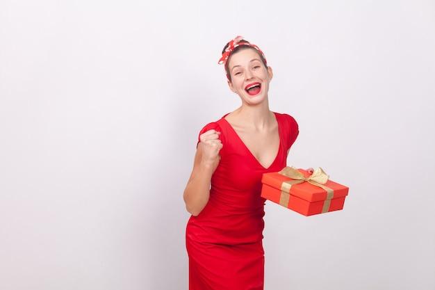예! 이기다! 선물 상자를 들고 성공 아름 다운 여자, 이빨 미소. 실내, 스튜디오 촬영, 회색 배경에 고립