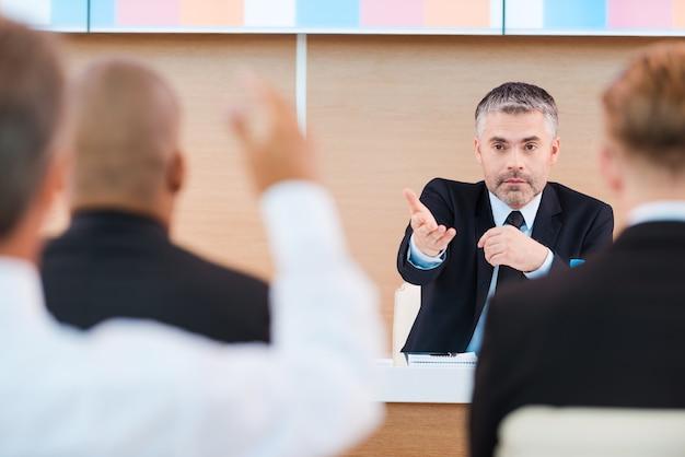 Да ты! уверенный в себе зрелый мужчина в формальной одежде, говоря слово кому-то из аудитории, сидя в конференц-зале