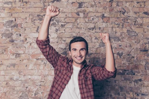 はい!上げられた握りこぶしで勝利する若い幸せな男