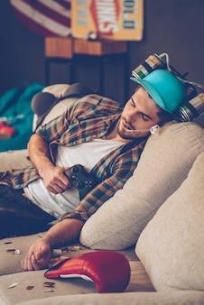 어제는 멋진 파티였습니다. 조이스틱을 들고 소파에 낮잠을 자는 맥주 모자를 쓴 젊고 잘생긴 남자