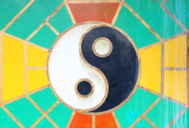 Yin yang sign on the grunge wall of chinese temple in thailand.