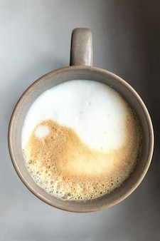 Yin yang sign on milk foam in coffee cup