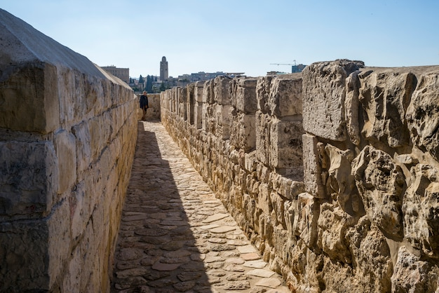 イスラエル、エルサレム、背景でymcaタワーで旧市街を取り囲む壁の遊歩道の眺め