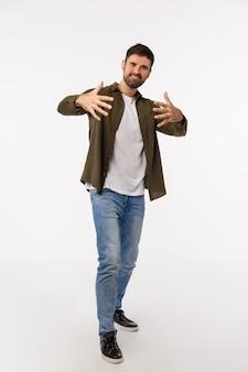 ヨマン。フルレングスの縦型スタジオは、クールでスタイリッシュなハンサムで自信を持って生意気な若いひげを生やした男、フリースタイル、ラップまたはヒップホップ、白い背景をダンスとして手でジェスチャー Premium写真