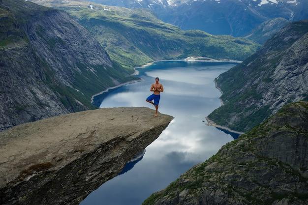 Йог молится на краю тролльтунга. odda. норвегия