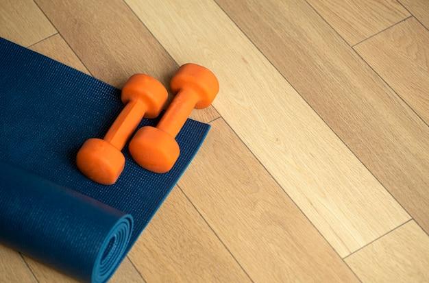 ヨガとフィットネスの背景フローリングの寄木細工の床またはラグとダンベルのラミネート