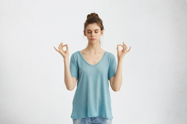 ヨガと瞑想。瞑想しながら目を閉じたままのカジュアルな服装の美しい若い女性