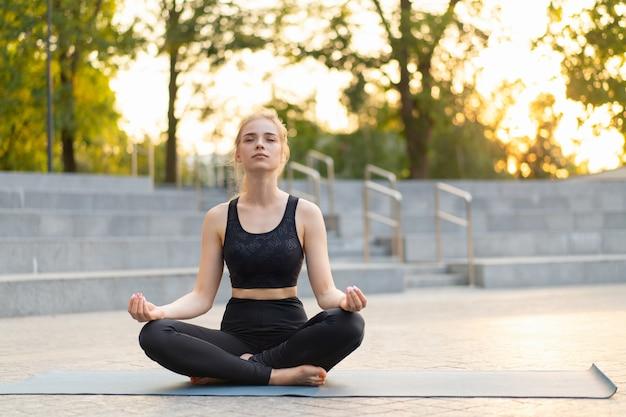 현대 도시 백인 여성의 요가와 명상 콘크리트 바닥에 야외 여름 공원에 앉아 요가 매트 요가 연습 후 휴식을 취하는 젊은 성인 여성 siddhasana 휴식
