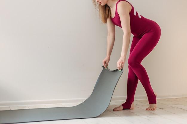 自宅でのヨガ瞑想ヨガのためのリビングルームでのアクティブなライフスタイルの女性のローリングエクササイズマット。屋内と屋外のトレーニング。スポーツと健康的なアクティブなライフスタイルのコンセプト。