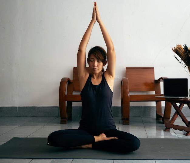 エクササイズスーツを着ている女性、マットの上に座って、一緒に手を押して頭の上に持ち上げ、目を閉じて、yoga.at home.relax時間の前に瞑想