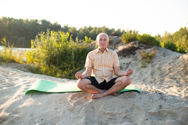 Yoga at beach. senior man in lotus pose sitting on sand. concept of calm and meditation.