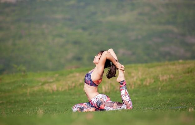 Йога: красивая молодая женщина, занимаясь йогой в парке летом. здоровый образ жизни. различные позы йоги.