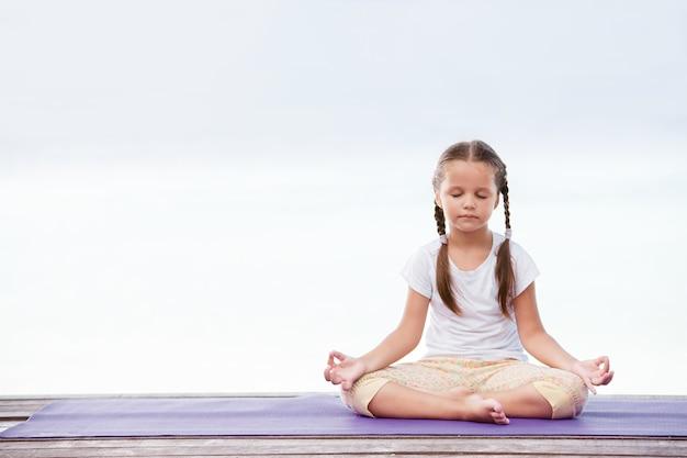 木製のプラットフォームで運動を瞑想するヨガの子供