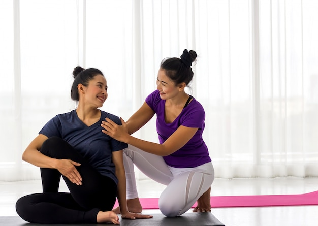Yoga class instructor helps beginner to make asana exercises. healthy lifestyle in fitness club. stretching with coach