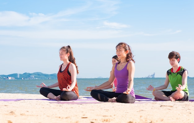 Yoga class at sea beach in sunny day ,group of people doing lotus pose with clam relax emotion