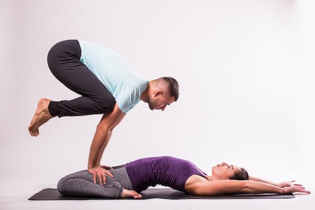 Концепция йоги. молодая здоровая пара в позе йоги на белом фоне