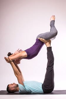 Concetto di yoga. giovani coppie in buona salute nella posizione di yoga su priorità bassa bianca