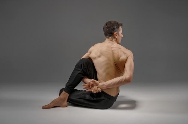 Йога делает упражнения на растяжку на сером фоне. сильный мужчина, практикующий йогу, обучение асанам, высшая концентрация, здоровый образ жизни
