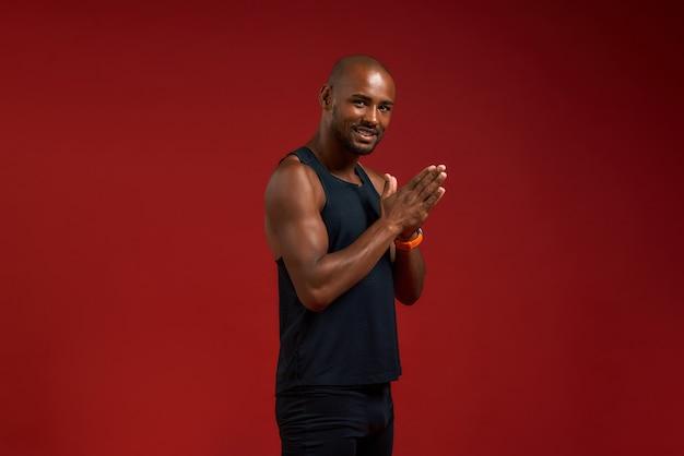 요가 연습 젊은 아프리카계 미국인 남자 손바닥을 함께 유지 하 고 미소로 카메라를 보고