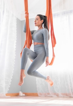 Йога летать крупным планом с молодой женщиной, практикующей гамак