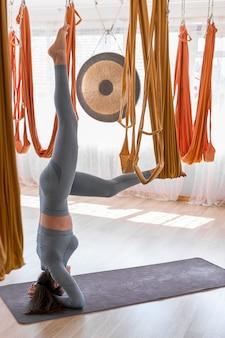 Учителя йоги демонстрируют, как висеть вверх ногами в гамаке.