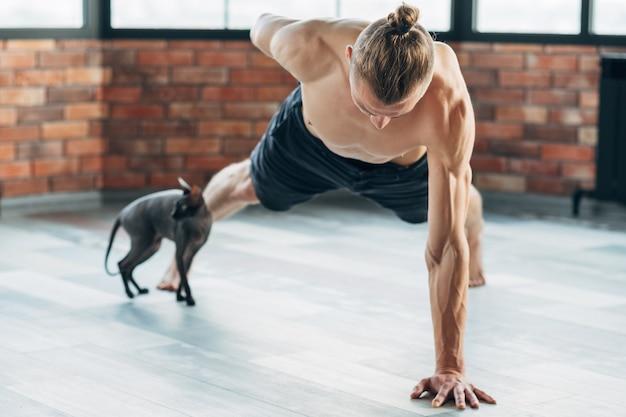 男性のためのヨガ。スポーツフィットネスとアスリートライフスタイル。強い体と引き締まった筋肉。ジムで持久力を行使する男。