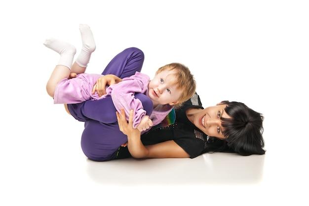 女性と子供のためのヨガ。運動をしている赤ちゃんを持つ母親
