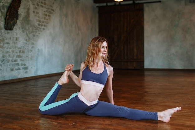 Йога девушка выполняет сложное упражнение на чердаке. эка пада раджакапотасана