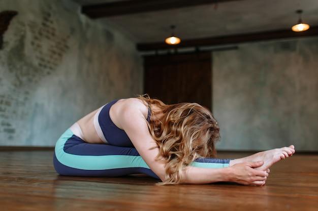 요가 소녀는 다락방에서 어려운 운동을 수행