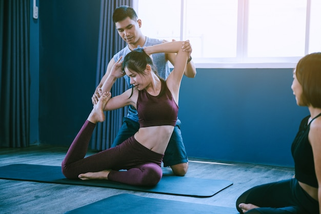 Yoga group concept; young man teaching woman practicing yoga in class; feeling calmness and relax in yoga class