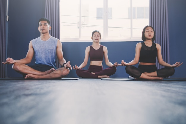 Yoga group concept; young people practicing yoga in class; feeling calmness and relax in yoga class