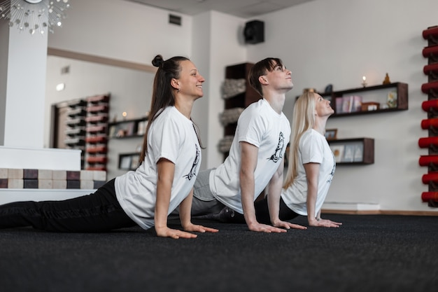 Yoga group lesson. girls and guy stretch their back muscles before training.