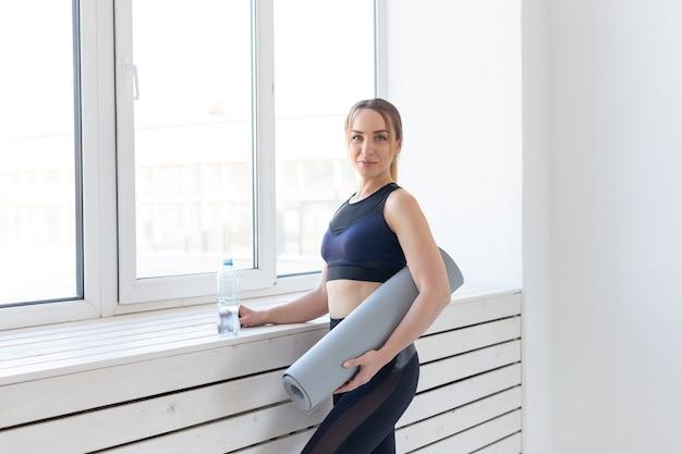 요가, 건강 및 스포츠 개념 - 회색 매트와 물 한 병을 들고 있는 젊은 여성.