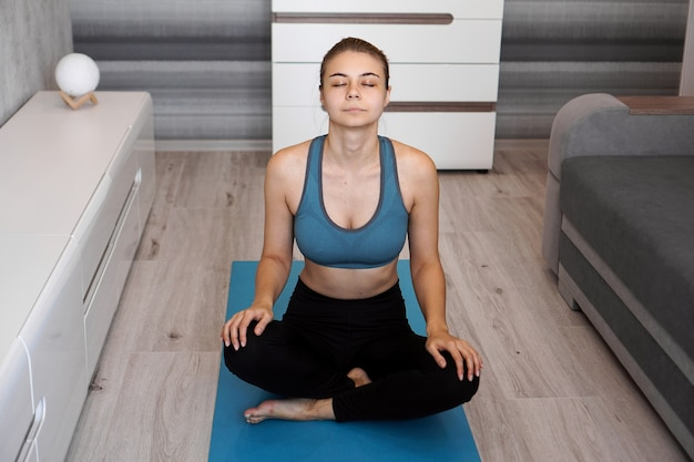 Yoga at home. keep calm. attractive young woman sitting on lotus position with eyes closed.