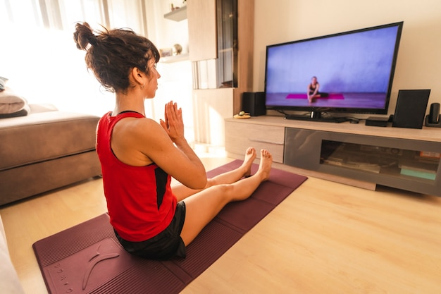 Yoga at home, a young woman meditating following the online instructions. in the coronavirus quarantine